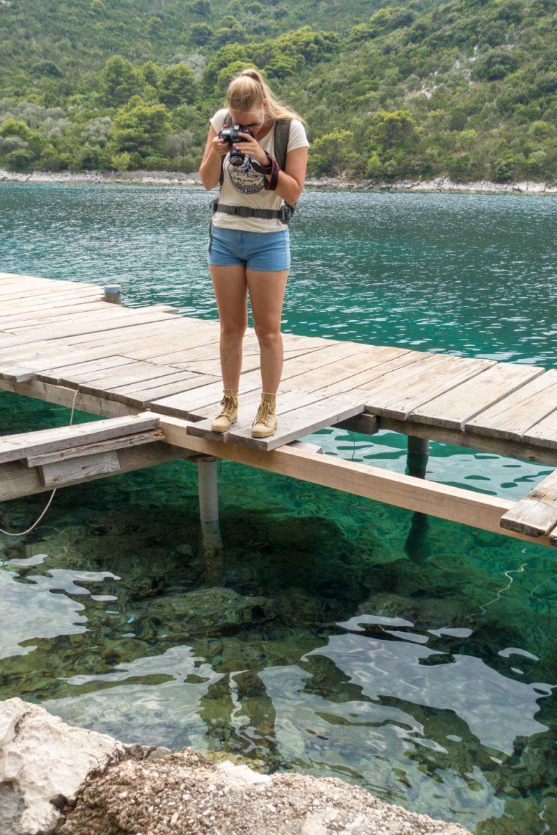 Manouk maakt een foto van het blauwe water onder de steiger in Okukulje
