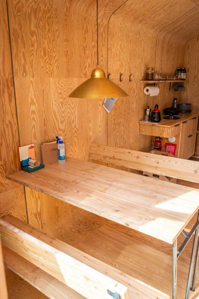 Houten tafel en banken en keuken op de achtergrond in een houten cabin