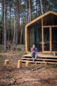 Manouk zit op het trapje voor een houten Cabiner in het bos bij de Sallandse Heuvelrug