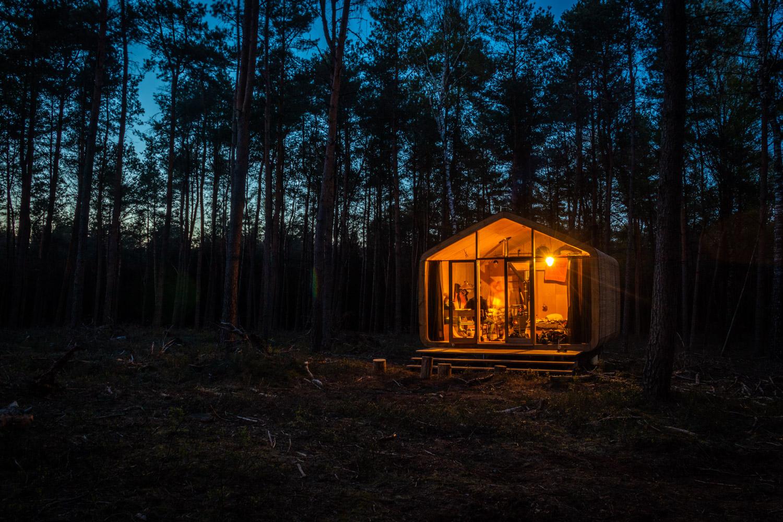 Cabiner in een donker bos op de Sallandse Heuvelrug met geelverlichte ramen