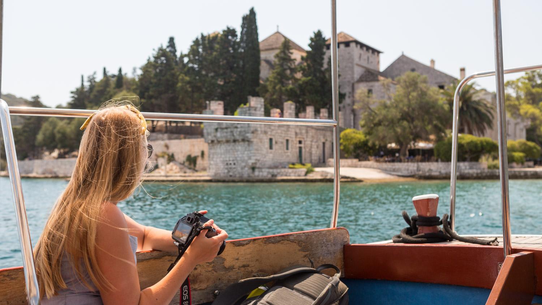 Manouk op een bootje naar Sveti Marija met op de achtergrond het klooster op het eilandje