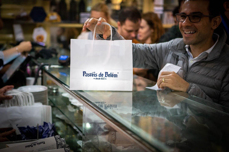 Een tasje met pasteis de nata wordt overhandigd aan een klant in Pastéis de Belém