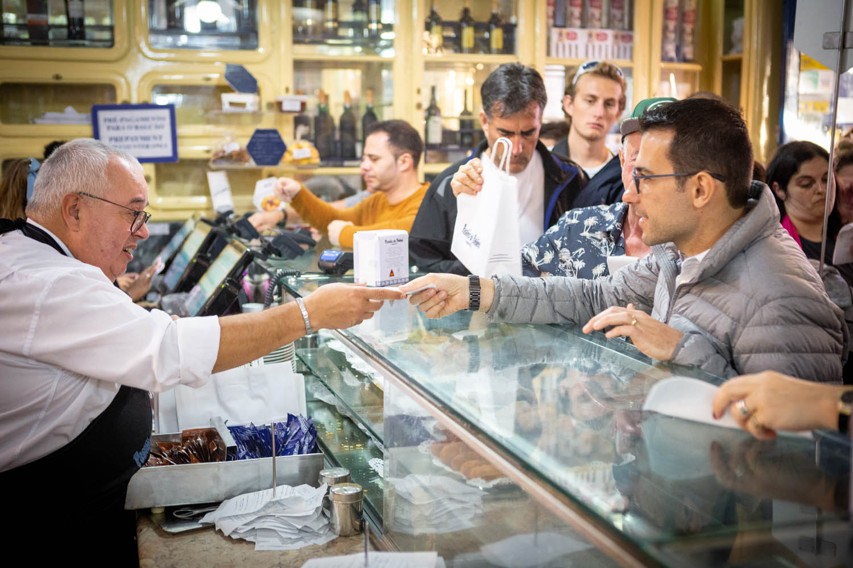 Drukte bij de toonbank van de zaak Pastéis de Belém in Lissabon