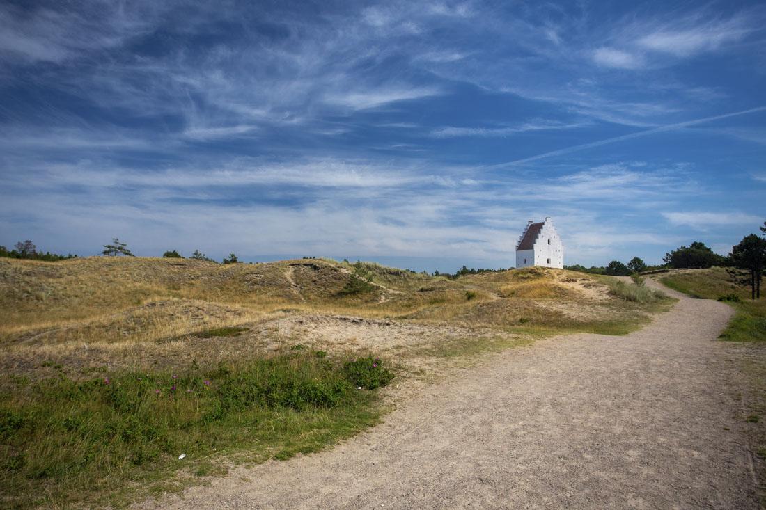 Den Tilsandede Kirke aan de rechterkant van de duinen met het pad ernaartoe en de blauwe lucht
