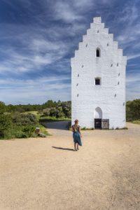 Manouk loopt over het zand voor de witte toren van Den Tilsandede Kirke met blauwe lucht