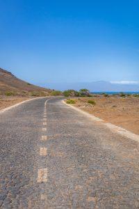 Een ;ange lege weg leidend naar de zee, met blauwe lucht en zand erlangs