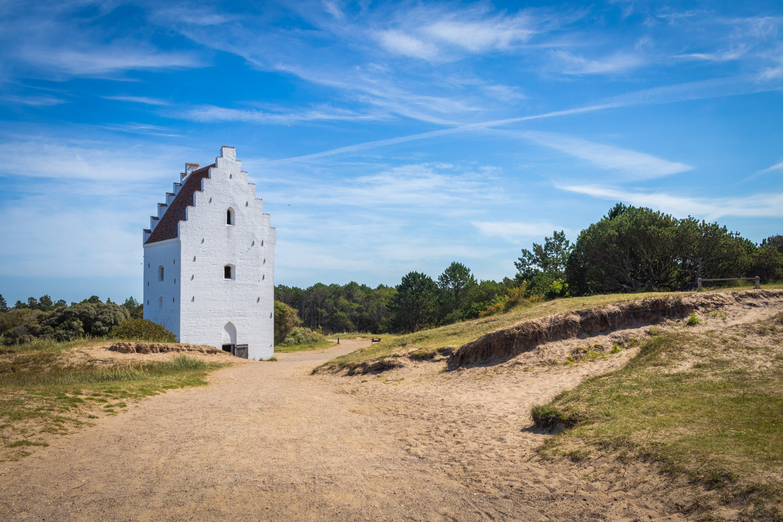Het witte kerkje tegen een blauwe lucht met een zandpad ernaartoe