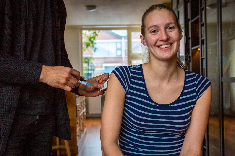 Manouk zit klaar voor haar eerste reisvaccinatie via Thuisvaccinaties.nl in de woonkamer