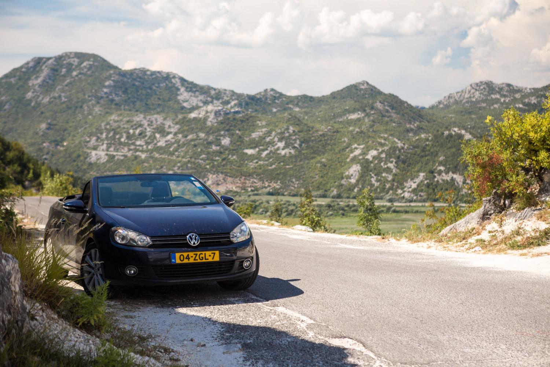 Volkswagen cabrio staat langs de weg naar het Skadarmeer in Montenegro met bergen op de achtergrond