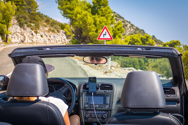 Manouk zit achter het stuur van een cabrio en kijkt in de achteruitkijkspiegel: autovakantie tips