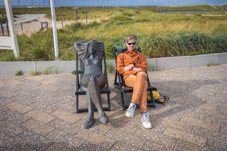 Beeld Vrouw in ligstoel in Katwijk met Hugo ernaast