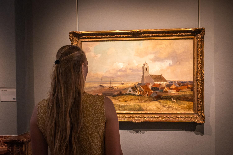 Manouk kijkt naar een schilderij in het Katwijks Museum